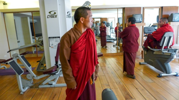 Monks work out at the gym in the luxury hotel, Uma Paro by COMO.