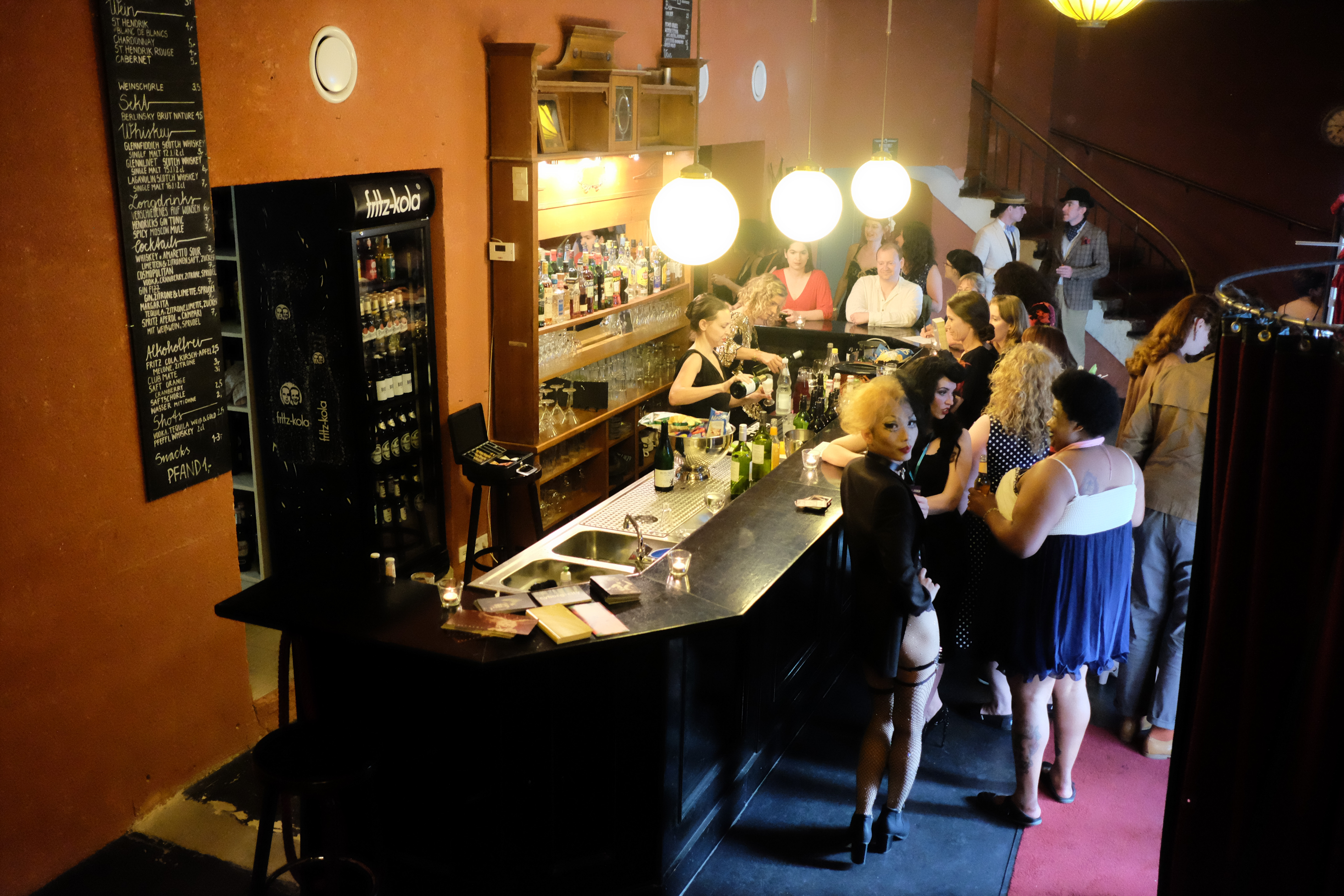 People crowd around the bar at Delphi theater during a Berlin Burlesque Week event.