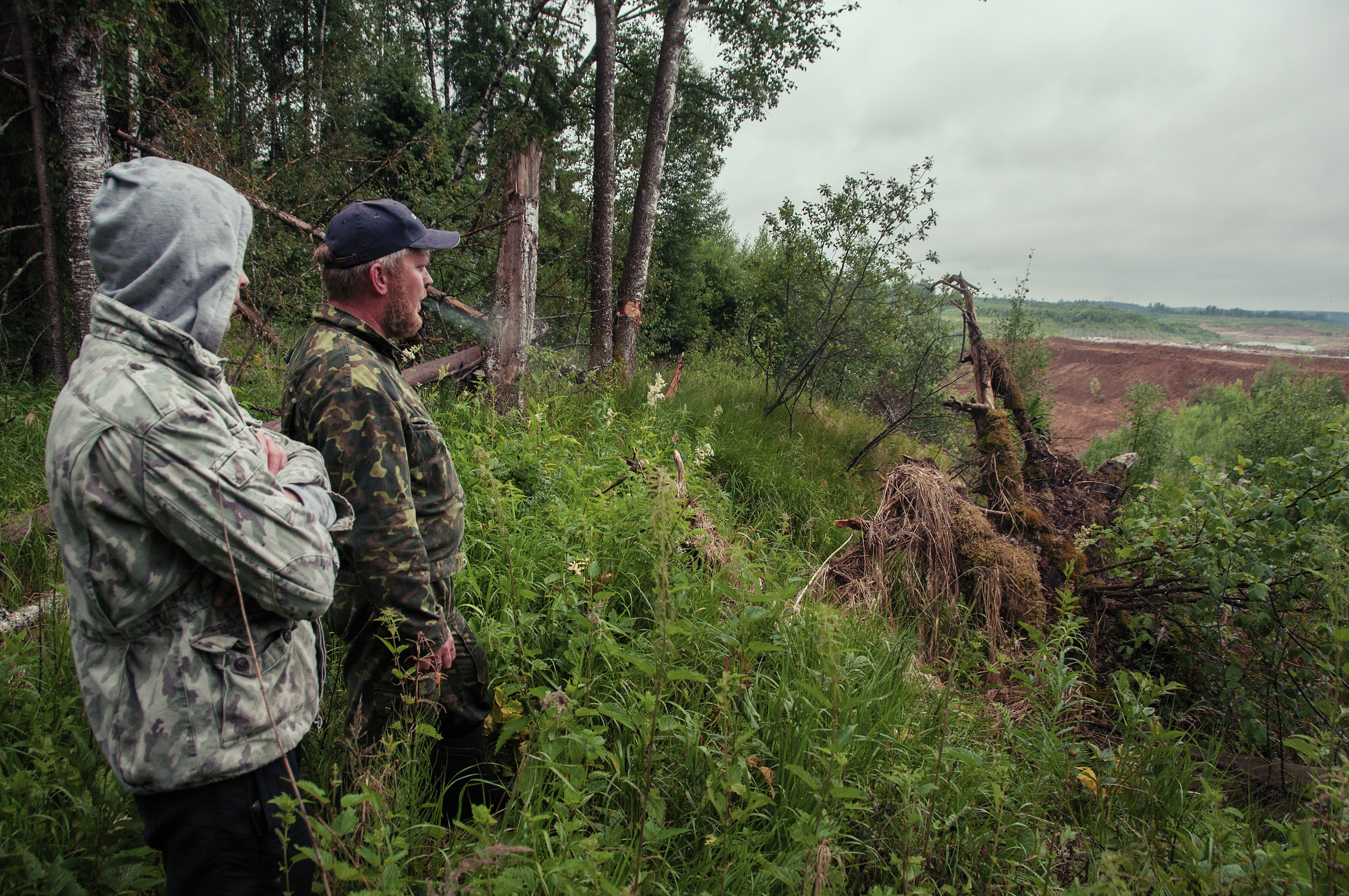 Kirill Artyukhov and a fellow activist stand at the edge of the forest overlooking the dumping site.