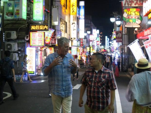 Bourdain and Masa Kokubo walk in Tokyo.