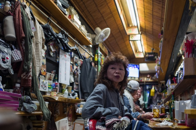1. Patrons at an izakaya in the Tokyo suburb of Saitama. 2. Sake bottles line the bar at an izakaya in Tokyo.