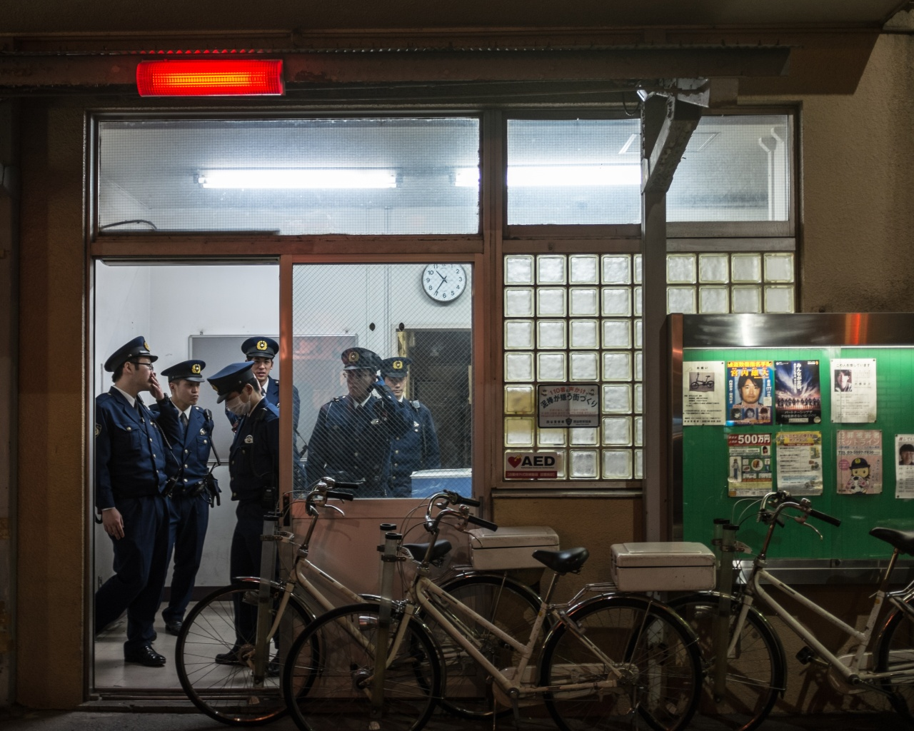 Japanese police officers mill about late night.
