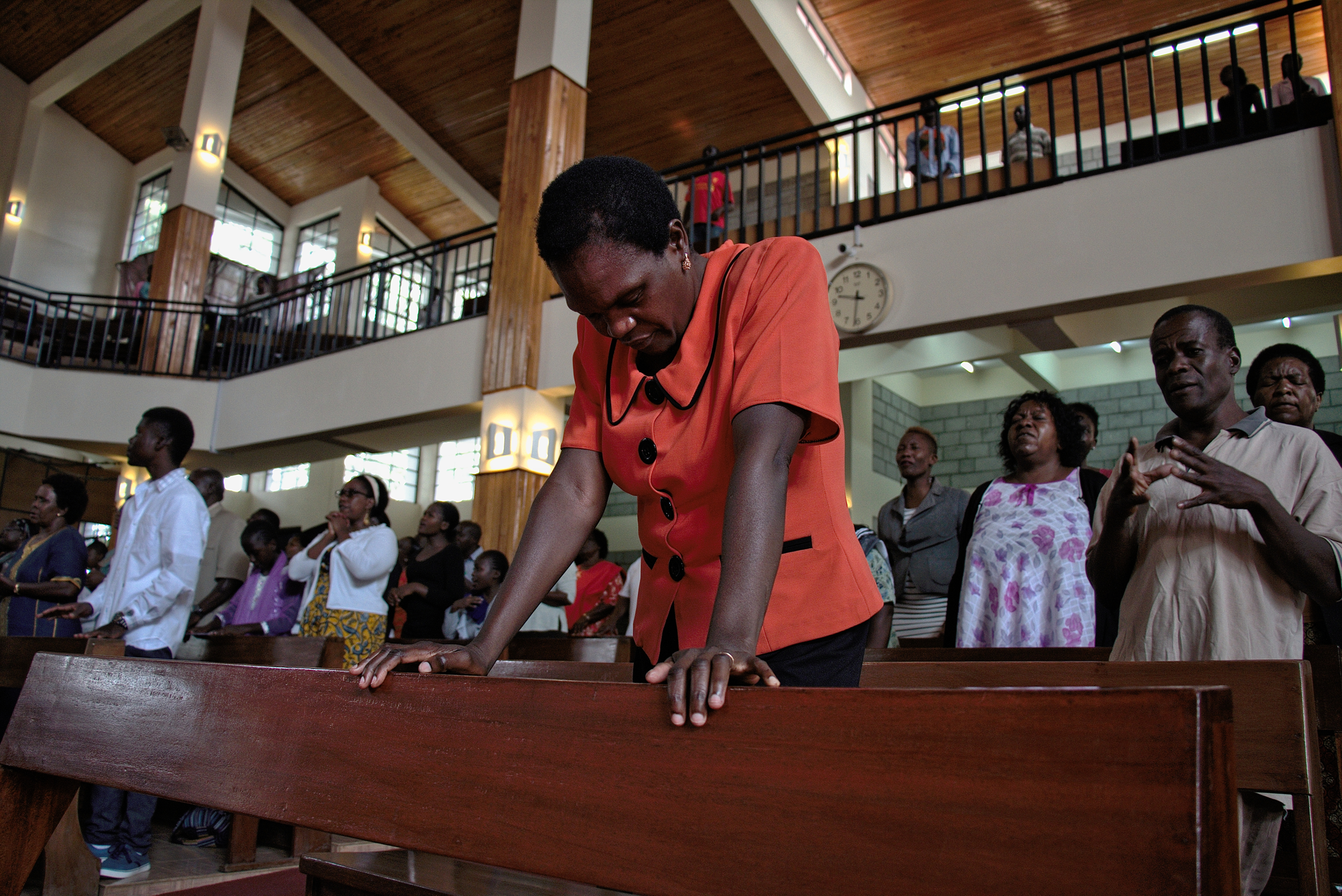 1. A woman's hands clasped in prayer during silent worship at the Friends International Centre in Nairobi, Kenya. 2. A churchgoer prays during a Sunday service at the Friends International Centre in Nairobi.
