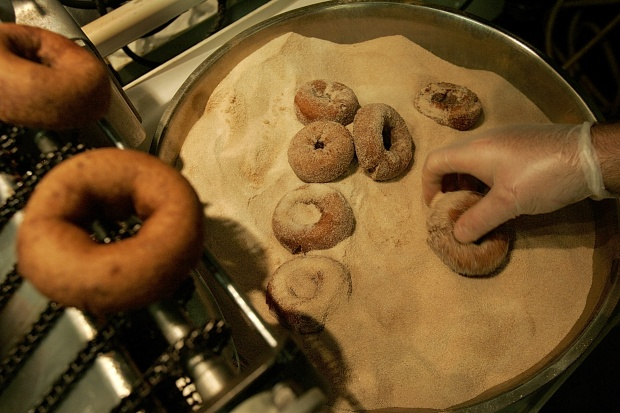 Cider doughnuts being dipped in sugar. Photo by Suzanne Kreiter / The Boston Globe via Getty Images.