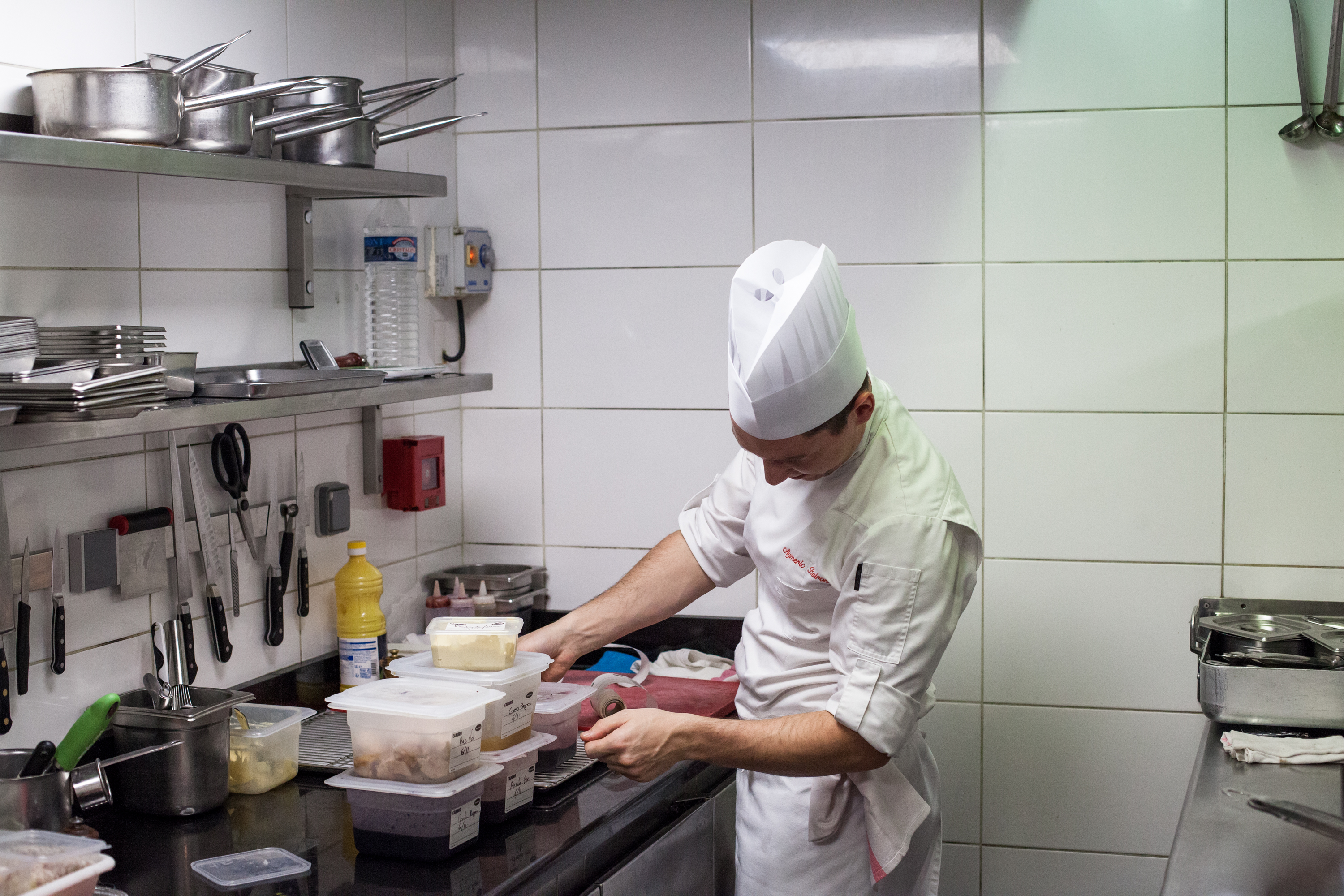 1. A chef measures ingredients to prepare for a lunch service. 2. Chefs at work while the service is starting.