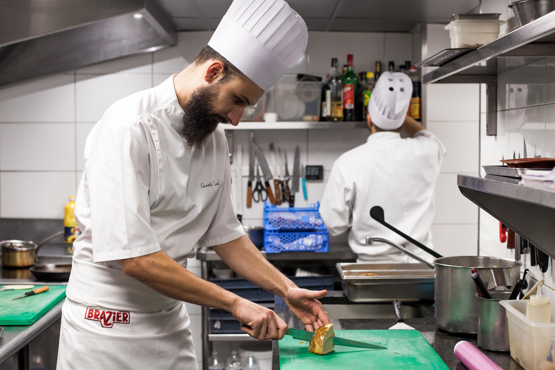 A chef cuts a fond d'artichaut au foie gras, a classic dish by Eugénie Brazier.
