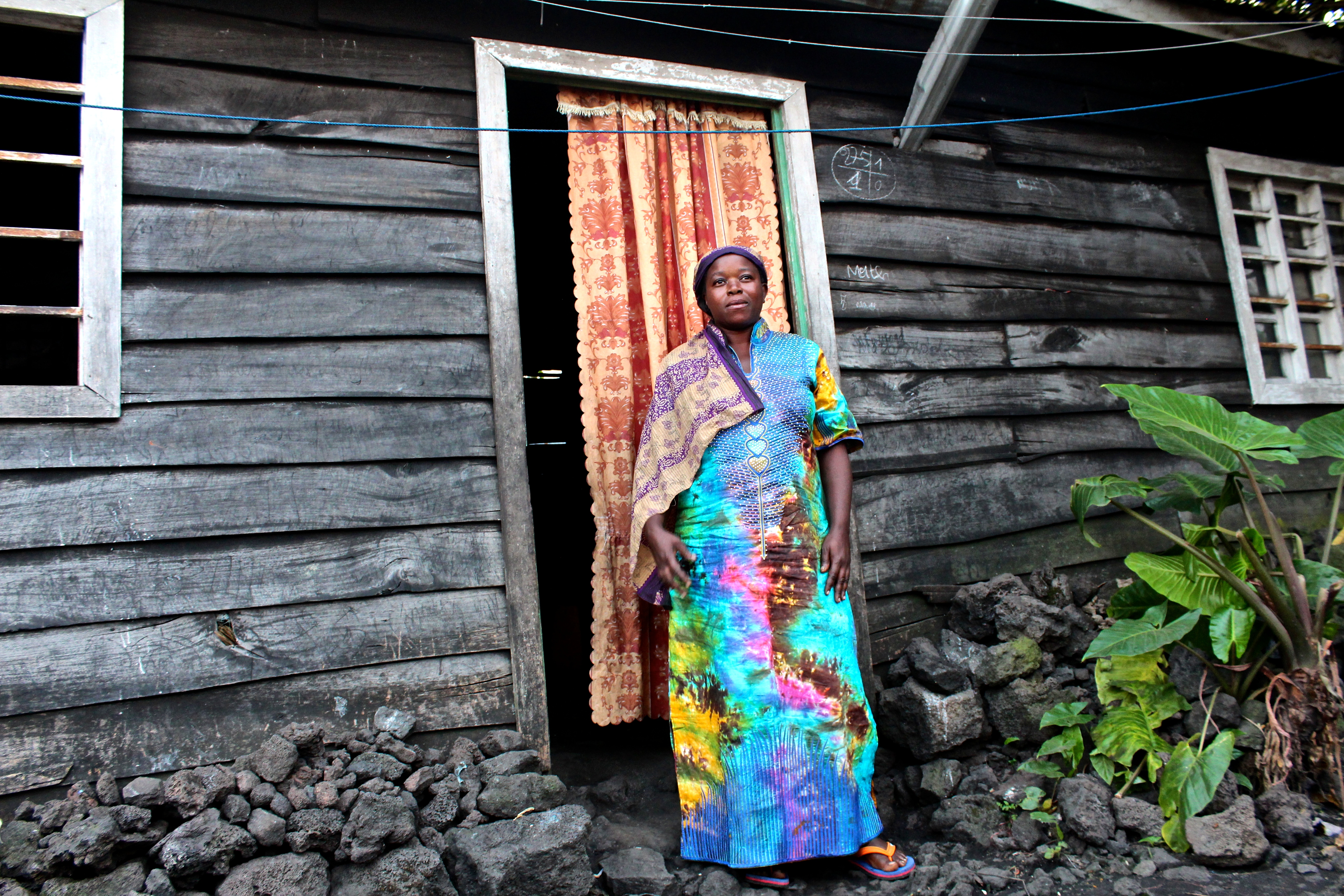 Kavira Ngesera, 41, standing in front of her home in Goma that she and her husband spent saving years to build.