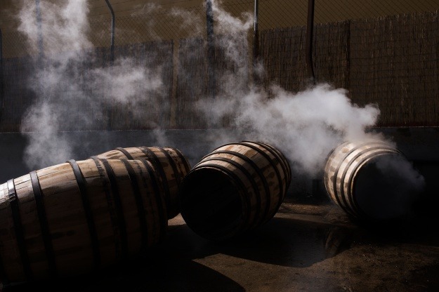 1: A cooper works on a cask. 2: Casks smoke after being toasted.