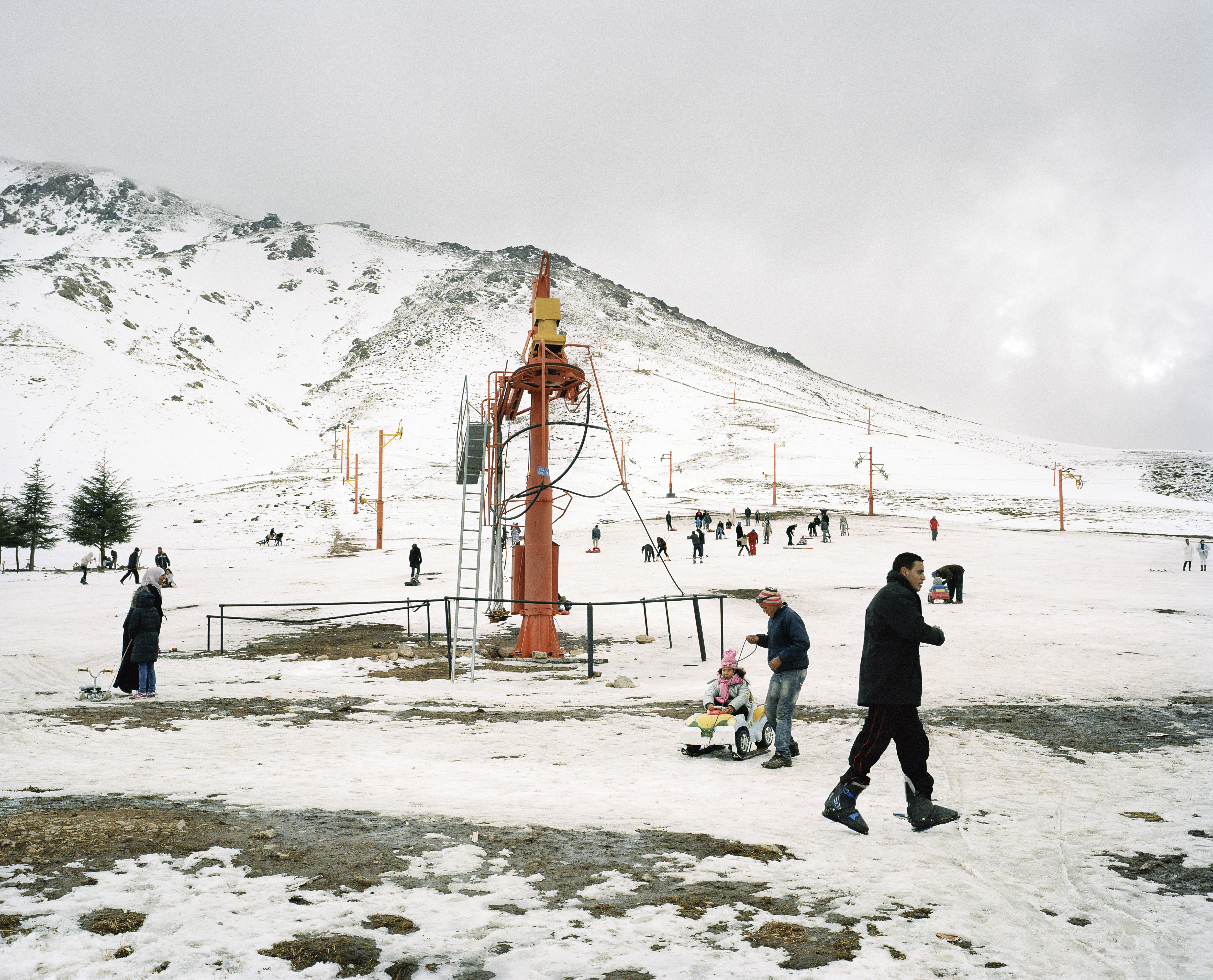 1: Dated skis at the summit of Jebel Oukaimeden. 2: People skiing and sledding down the slopes at the resort.