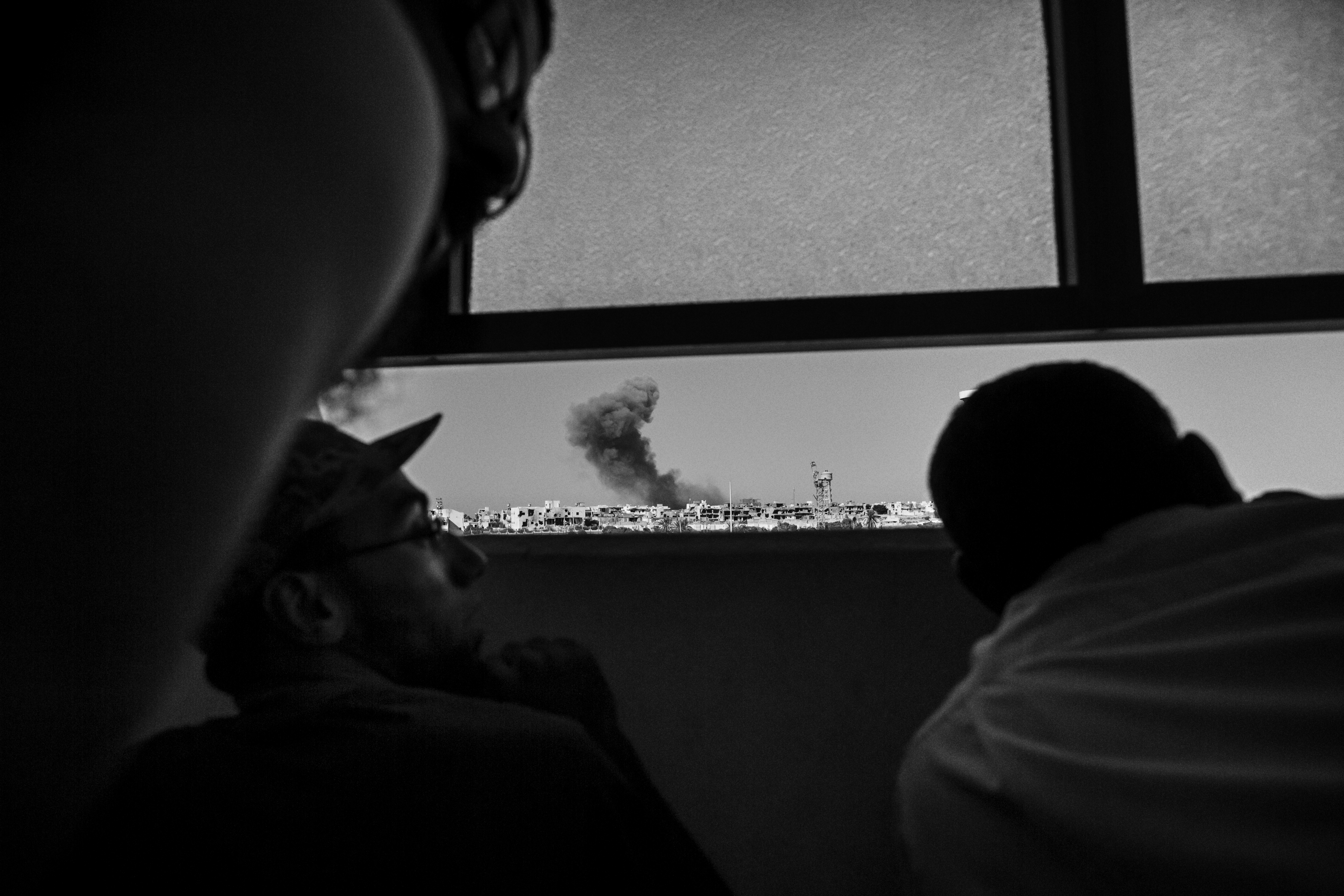 Members of the Libyan forces, affiliated with the Tripoli government, watch an airstrike on ISIS positions in Sirte - September 2016.