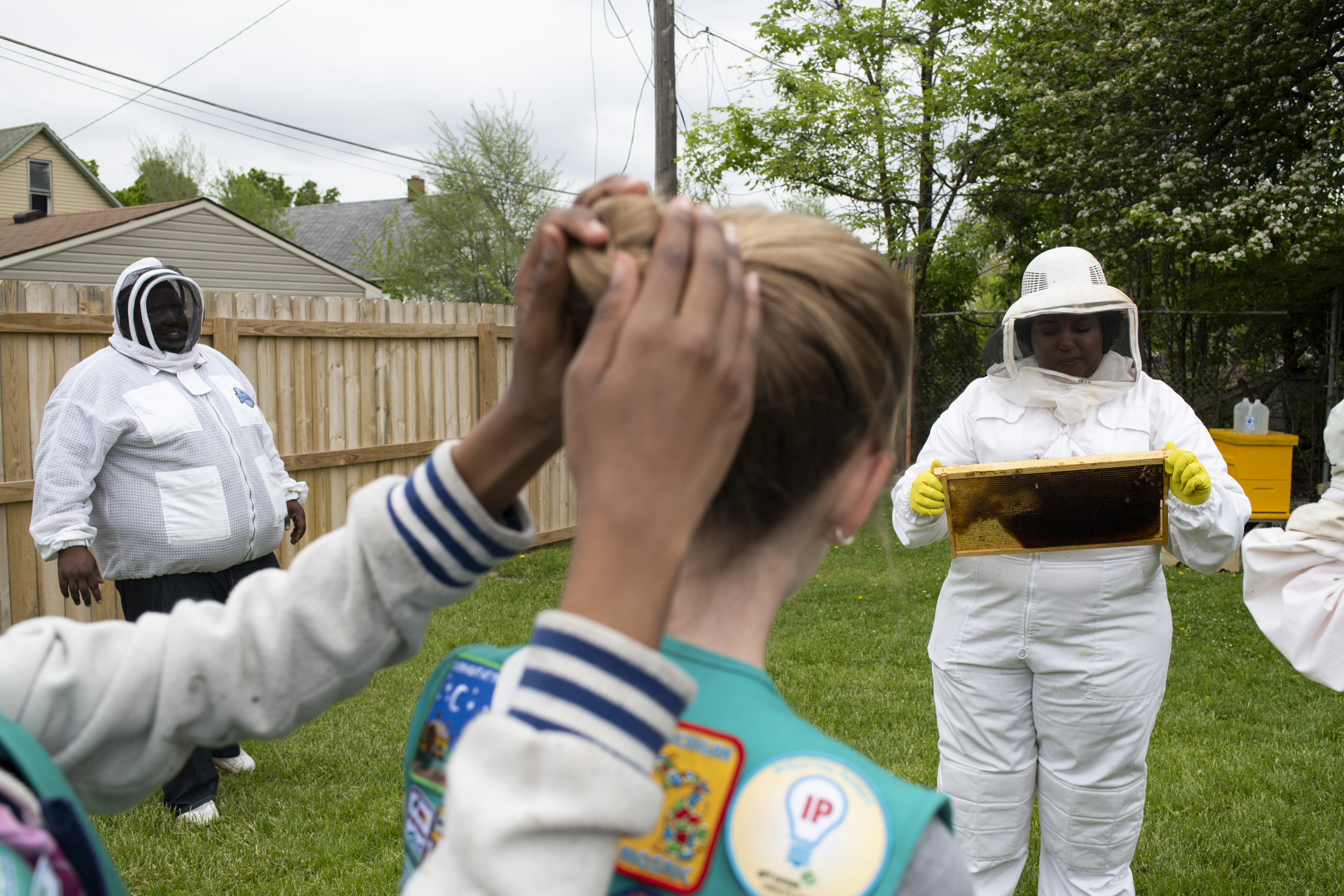 Lindsey displays a frame with bees during a hive inspection for Girl Scout Troop 40035 members.