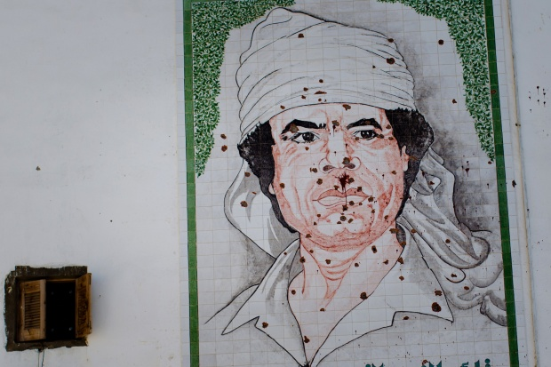 A mosaic of Gaddafi is seen on the wall of a building, riddled with bullett holes, on August 29, 2011 in Tripoli. Photo by Daniel Berehulak via Getty Images.