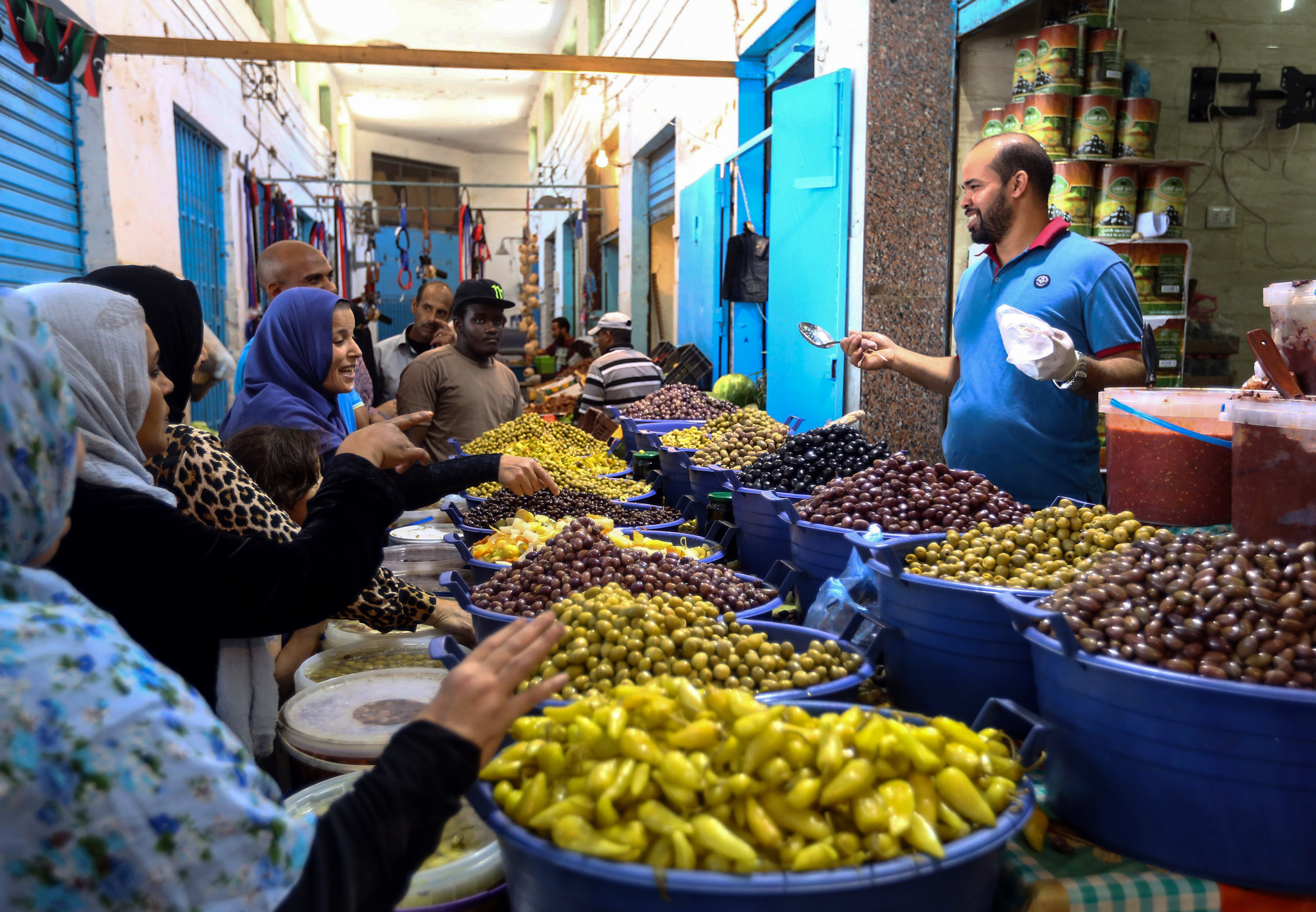 1: A tourist shops for souvenirs at a market in the old city of Tripoli. Photo by Joseph Eid/AFP via Getty Images. 2: Libyans shop for olives and pickles at a market in the center of the capital Tripoli. Photo by Mahmud Turkia/AFP/Getty Images.