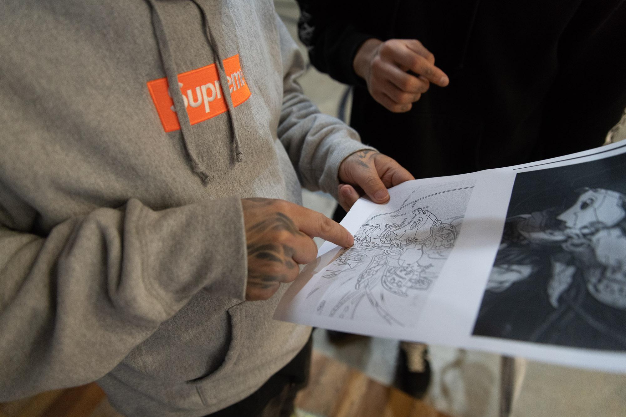 A tattoo artist and his client discuss a design inside Shen Tattoo Studio.