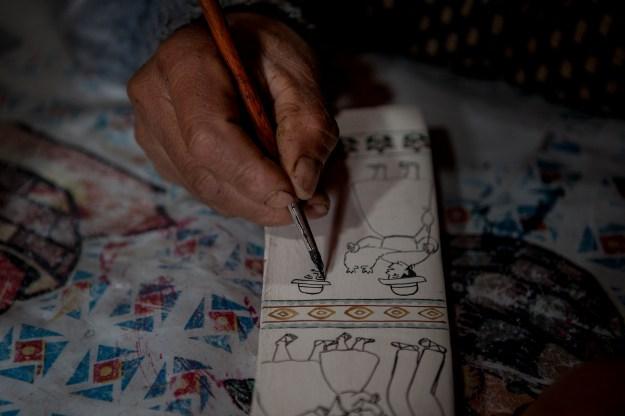 1: Venuca Evanán working on a tablas. 2: Porfirio Ramos works on a painting.