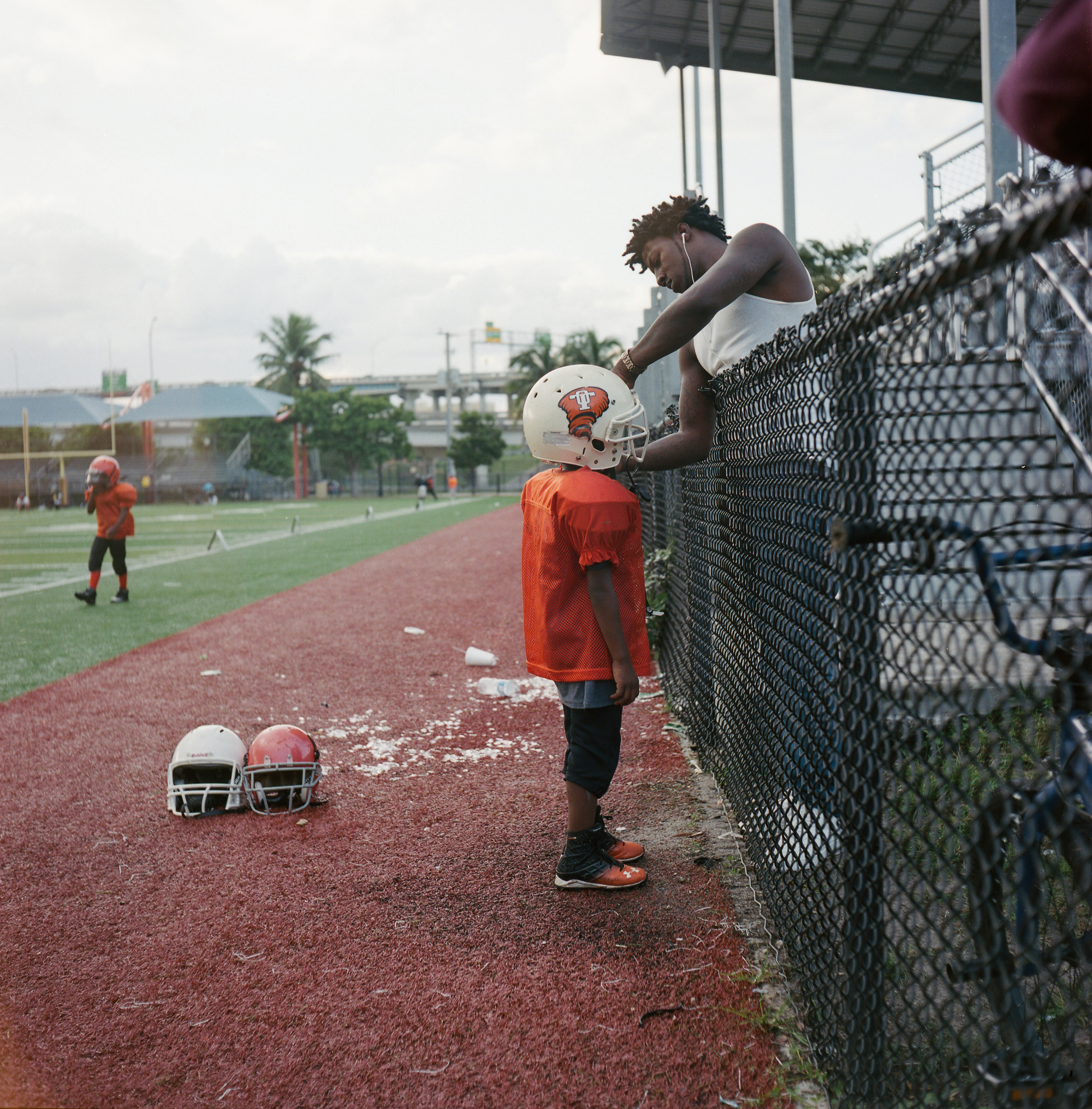 A father adjusts his son's helmet during an Overtown Tornadoes football practice.